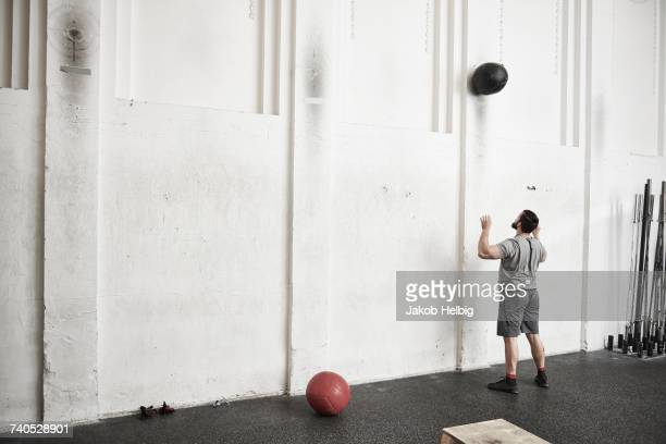 Man throwing fitness ball against wall in cross training gym