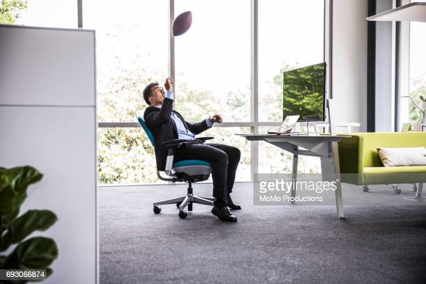 Man throwing football in modern business office