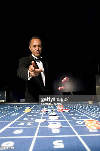 man throwing gambling chips across a roulette table - gambling table stock pictures, royalty-free photos & images