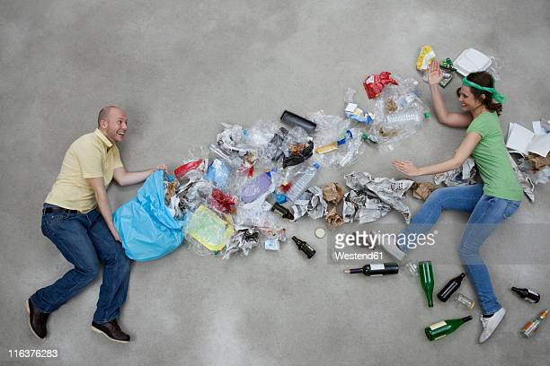 Man throwing garbage towards woman