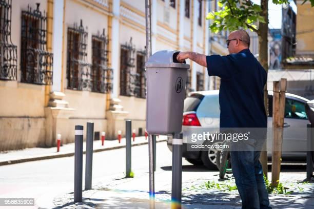 街の屋外のゴミ箱にゴミを投げる男 - クルジュナポカ ストックフォトと画像