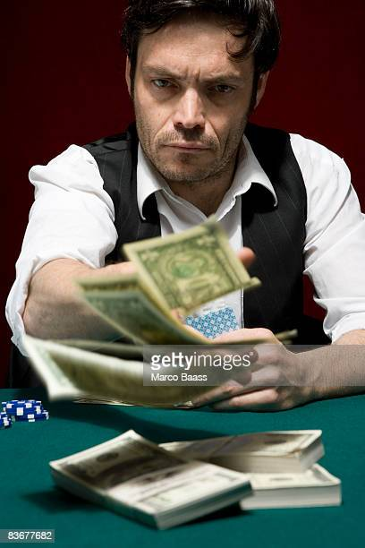 A man throwing money into the pot at a high stakes poker game