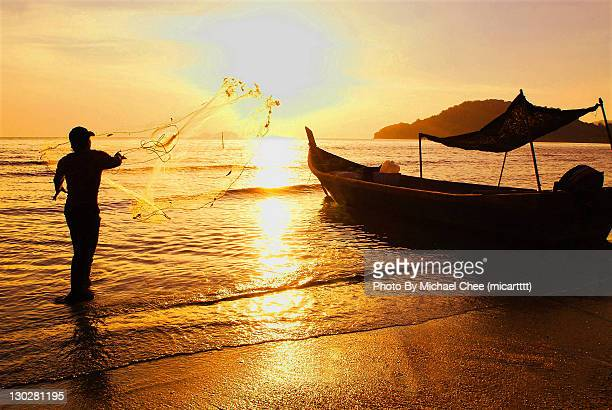 man throwing net in sea - george town penang stock photos and pictures