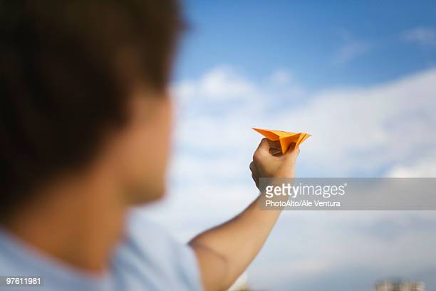 Man throwing paper airplane