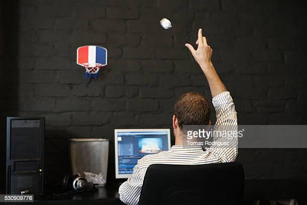 Man throwing paper in to wastebasket
