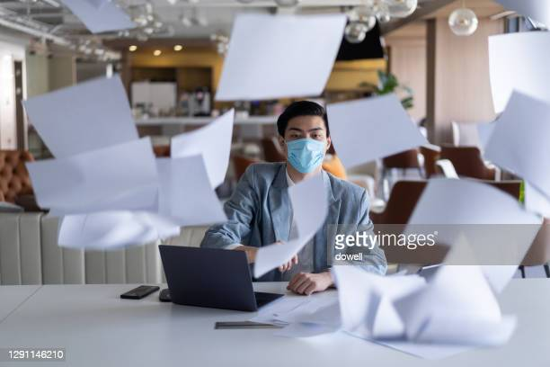 man throwing papers in air at office - document stock pictures, royalty-free photos & images