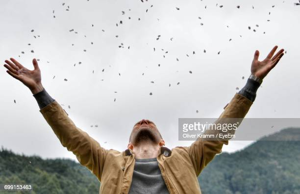 man throwing petals against sky - brown jacket stock pictures, royalty-free photos & images