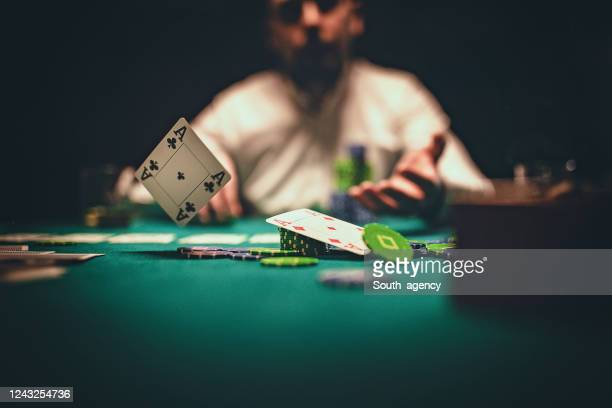 man throwing playing cards on table - gambling table stock pictures, royalty-free photos & images
