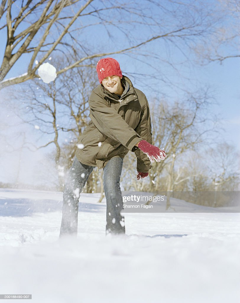 Man throwing snowball smiling, portrait : Stock Photo
