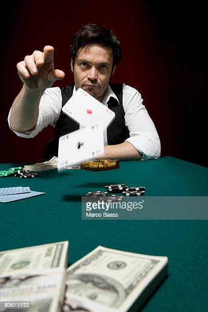 a man throwing two ace cards at a high stakes poker game - トランプのエース ストックフォトと画像