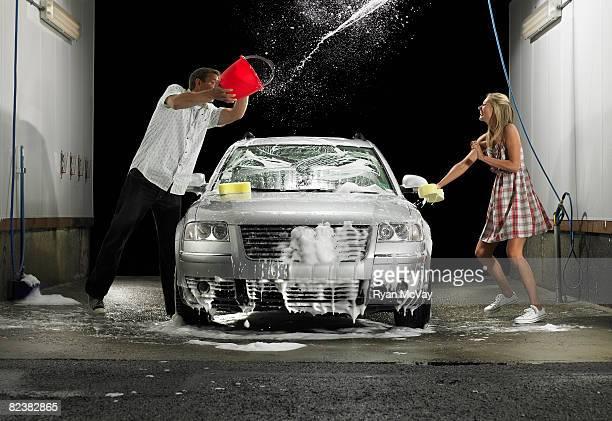 Man throwing water at woman while washing car