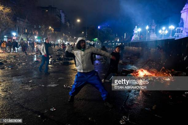 A man throws a bottle to riot police agents outside the National Congress in Buenos Aires Argentina on August 9 after senators rejected the bill to...