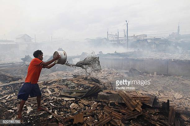 A man throws a bucket of water to put out smoldering remains of a fire in a slum area next to railway tracks in Kampung Bandan Fire destroyed...