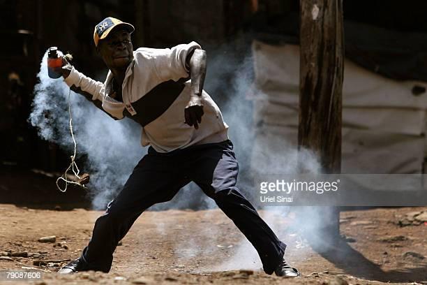 A man throws a canister at Kenyan police as he demonstrates in the Kibera slums January 17 2008 in Nairobi Kenya International mediators have...