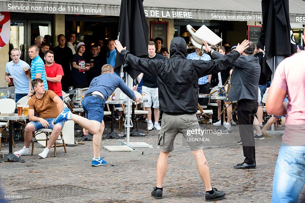 A man throws a chair as a small group of Russian men provoke a group of England supporters in the centre of Lille, on June 14, 2016, three days after Russia and England football fans clashed in the southern French city of Marseille during the Russia vs England, group B, Euro 2016 match. / AFP / LEON