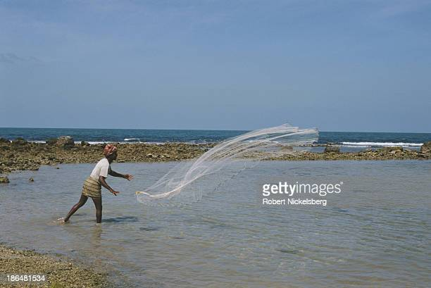 A man throws a fishing net in Valvettithurai hometown of Liberation Tigers of Tamil Eelam leader Velupillai Prabhakaran Jaffna Sri Lanka circa 1998