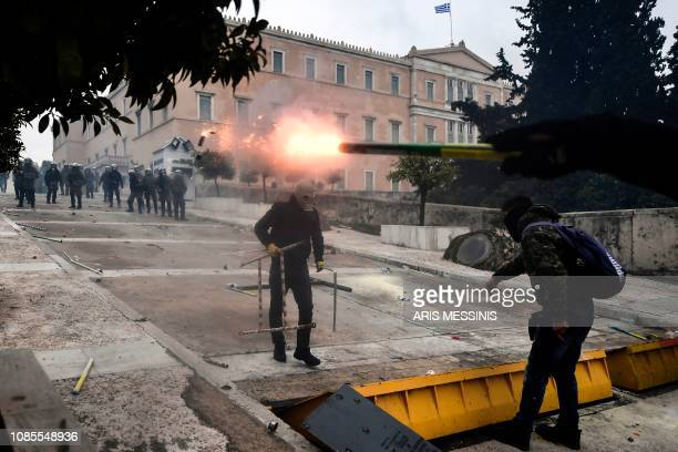 A man throws a flare at riot police in front of the Greek Parliament in Athens on January 20 2019 during a demonstration against the agreement with...