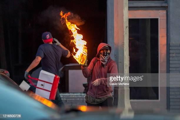 A man throws a Molotov cocktail as another loots a business on Melrose Avenue in the Fairfax District during demonstrations following the death of...
