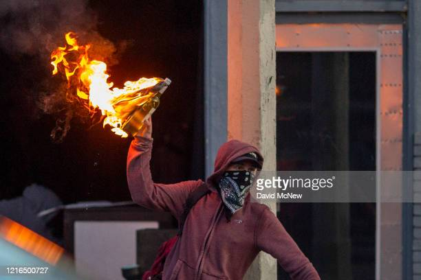 A man throws a Molotov cocktail on Melrose Avenue in the Fairfax District during demonstrations following the death of George Floyd on May 30 2020 in...