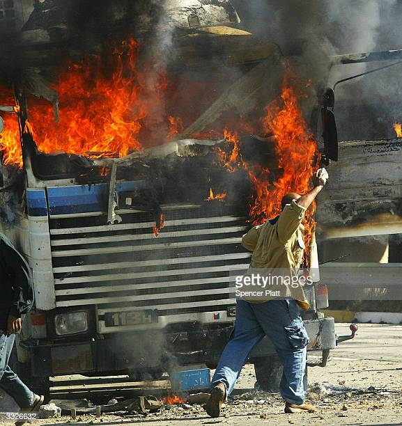 A man throws a rock at a burning truck that was part of a US military convoy which came under attack April 10 2004 in Baghdad Iraq Much of Iraq is...