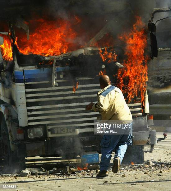 A man throws a rock at a burning truck that was part of a US military convoy that came under attack April 10 2004 in Baghdad Iraq Much of Iraq is...