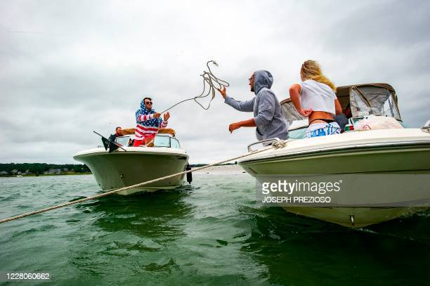 A man throws a rope to raft up his boat to another at Wingaersheek Beach in Gloucester Massachusetts on August 15 2020 Over the past summer weekends...