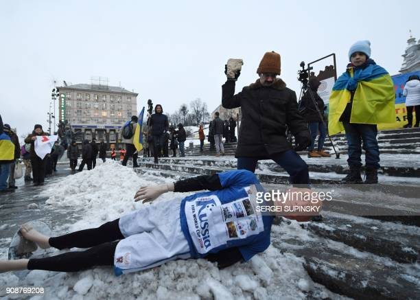 A man throws a stone at a mannequin depicting Russian President Vladimir Putin dressed in a football uniform during the 'Stop Putin Stop war' rally...