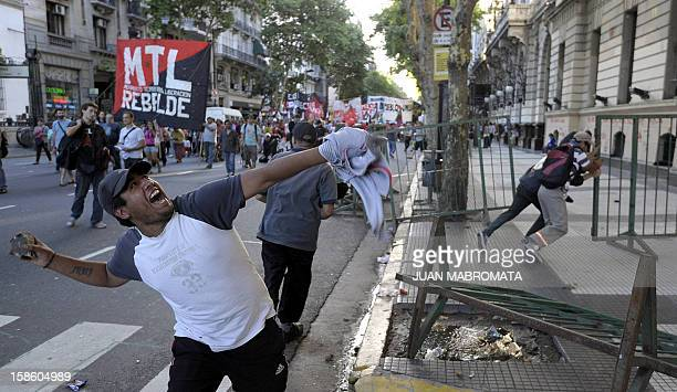 A man throws a stone at City Hall on December 20 2012 in Buenos Aires during a demonstration on the 11th anniversary of the clashes that took place...