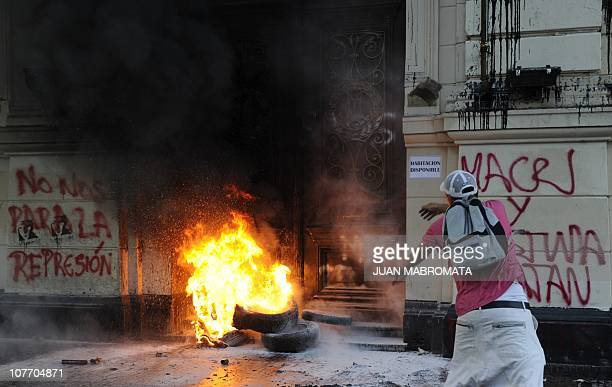 Man throws a stone at the door of Buenos Aires City Hall on December 20 during a demonstration in memory of the 30 deaths during clashes under the...