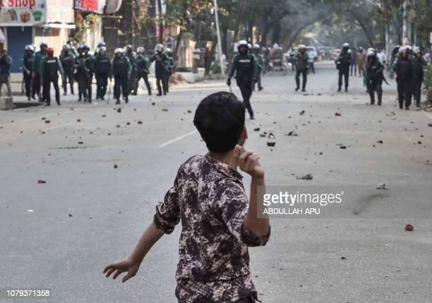 TOPSHOT A man throws a stone towards police during clashes as Bangladeshi striking garments workers march in the streets of Dhaka on January 8 2019...