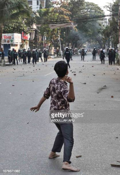 A man throws a stone towards police during clashes as Bangladeshi striking garments workers march in the streets of Dhaka on January 8 2019 during a...