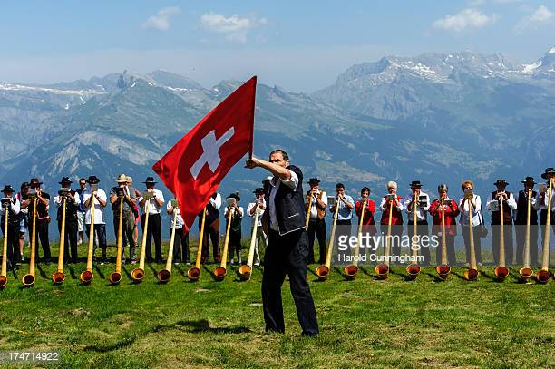 A man throws a Swiss flag as alphorn players perform on July 28 2013 in Nendaz Switzerland About 150 alphorn blowers performed together on the last...