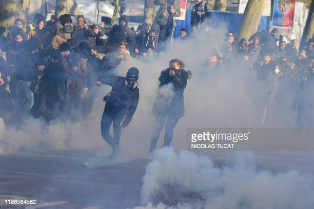 TOPSHOT A man throws a tear canister back as people stand amid tear gas smoke during a demonstration against the pension overhauls in Bordeaux on...