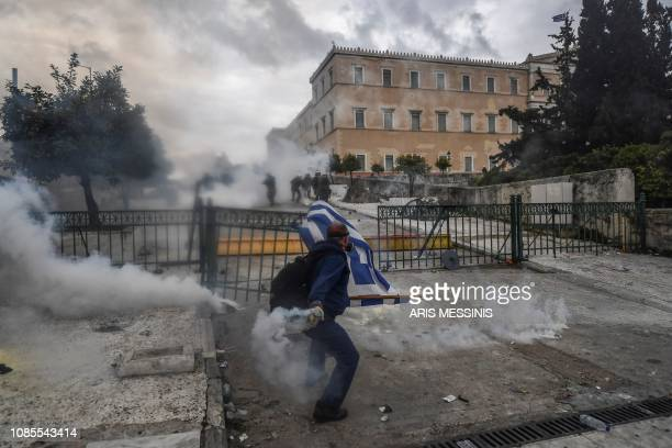 A man throws a tear gas canister as protesters clash with riot police near the Greek Parliament in Athens on January 20 2019 during a demonstration...