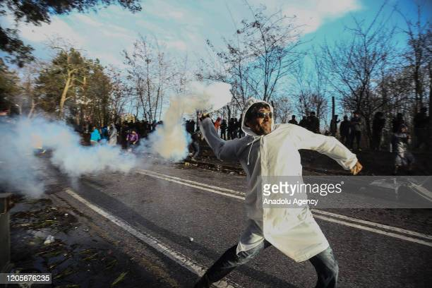 Man throws a tear gas canister back Greek police as Greek security forces use tear gas and water cannon to disperse asylum seekers in the region...