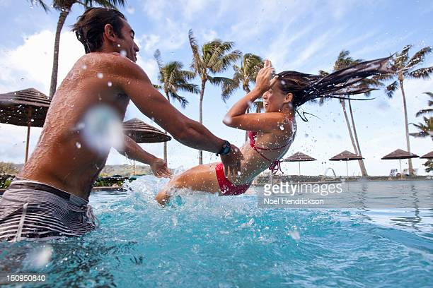 a man throws a woman into a pool - throwing stock pictures, royalty-free photos & images