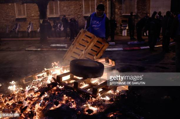 A man throws a wooden palette onto a fire as prison guards block access to Fresnes prison on January 16 2018 to demand tighter security after three...