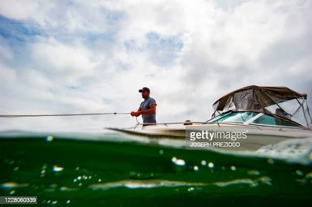 A man throws anchor to keep his boat at the beach at Wingaersheek Beach in Gloucester Massachusetts on August 15 2020 Over the past summer weekends...
