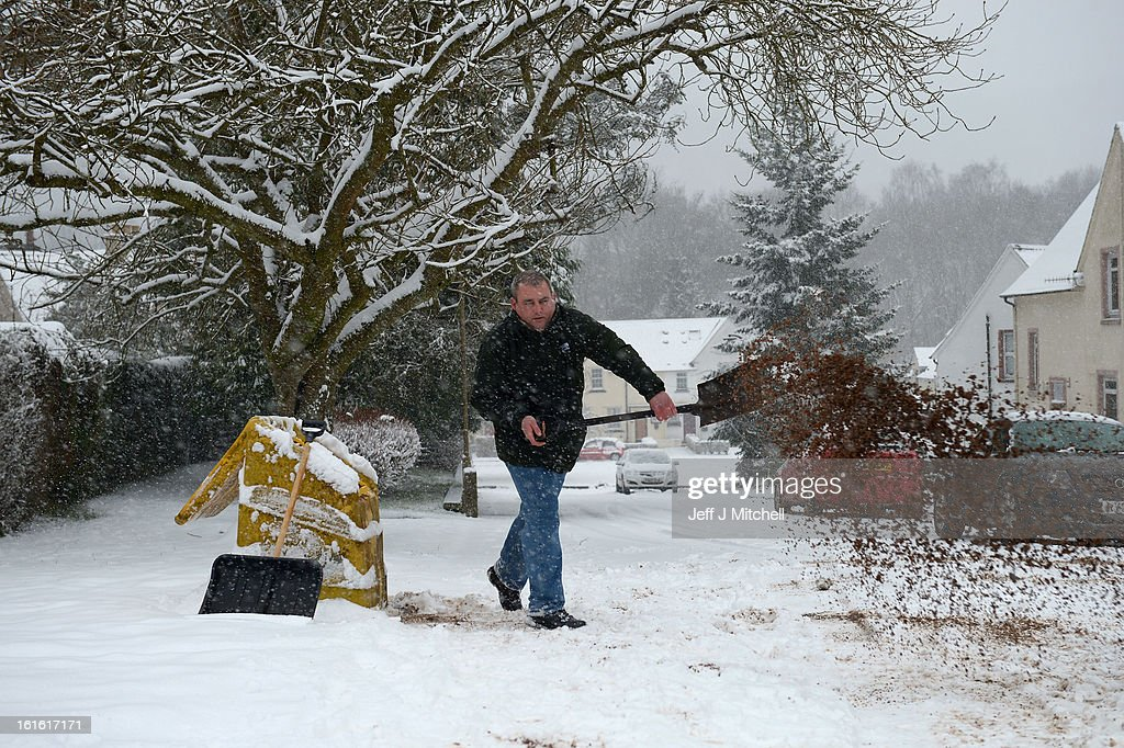 A man throws down salt on a road on February 13, 2013 in Blanefield, Scotland. Weather forecaster have issued a yellow weather warning of up to 10cm of snow on higher routes, with the possibility of travel disruption.