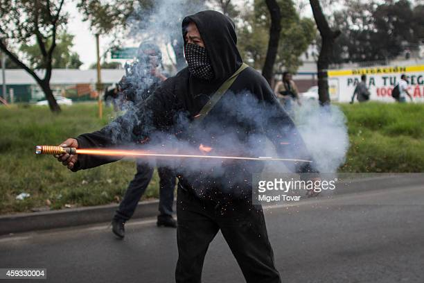 Man throws firecrackers to the riot police during the global protests against Mexican president Enrique Pena Nieto and his government after...