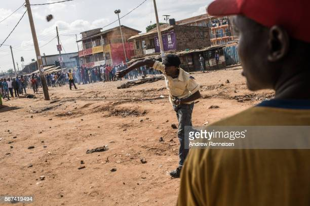 A man throws rocks into a residential compound that men were attempting to loot in the Kawangware slum on October 28 2017 in Nairobi Kenya Protests...