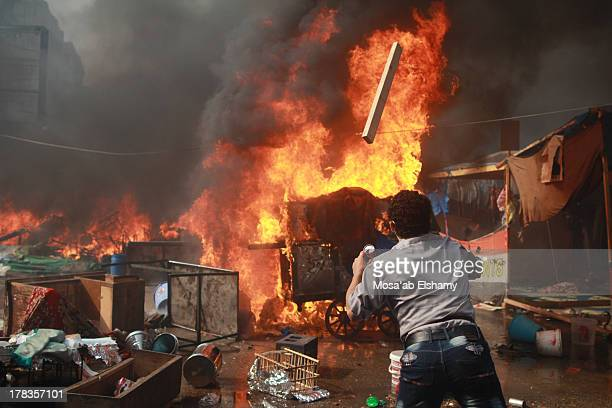 Man throws wood into the fire during clashes that broke out after Egyptian security forces stormed two huge protest camps at the Rabaa al-Adawiya and...