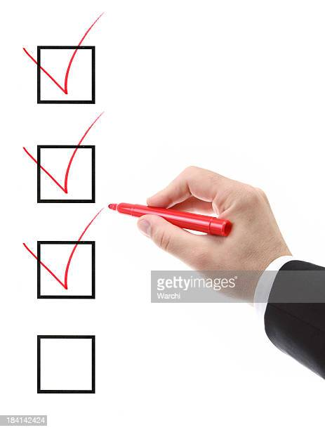 a man ticking check boxes with a red marker - checkbox stock photos and pictures