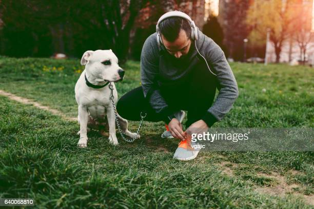Man Tie Shoelaces With His Dog Outdoors.