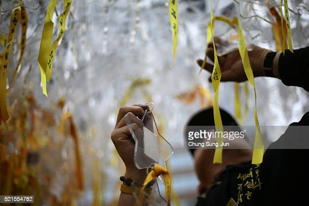 A man ties a yellow ribbon tribute to the victims of the sunken ferry Sewol during the second anniversary of the Sewol disaster on April 16 2016 in...