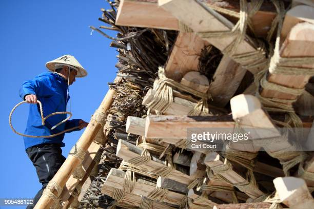 A man ties rope during construction of the shrine during preparations for the Nozawaonsen Dosojin Fire Festival on January 15 2018 in Nozawaonsen...
