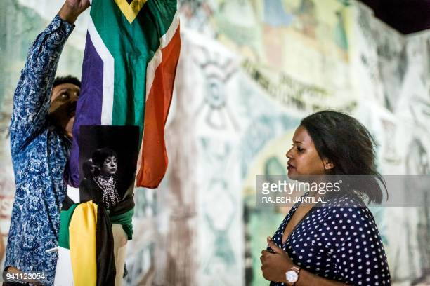 A man ties the South African flag to a pole close to the Old Durban Prison's Human Rights wall as he pays his respect to the late South African...