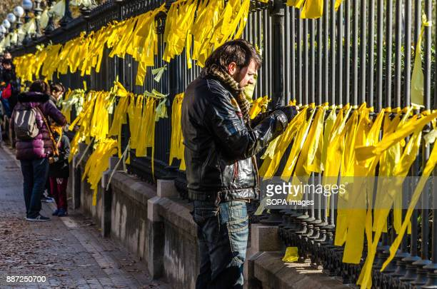 A man ties yellow ribbons to the gate of the Parc de la Ciutadella Support to the independence movement are continuous in Catalunya This morning...