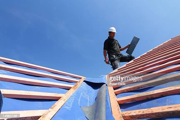 man tiling roof