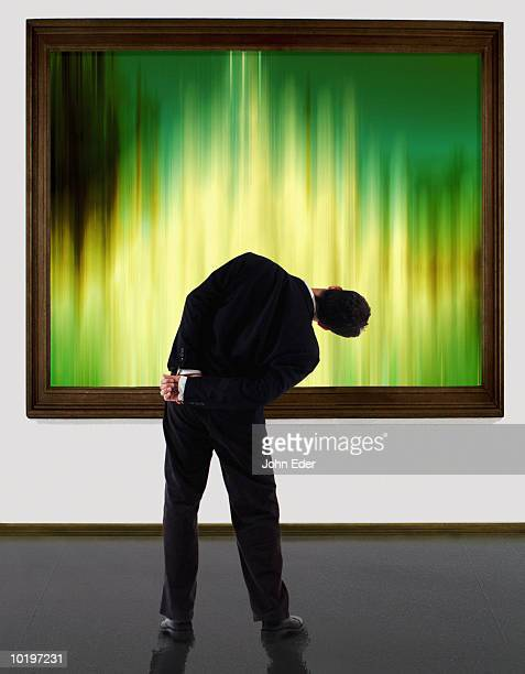 man tilting head upside down looking at painting, (digital composite) - man bending over from behind stock photos and pictures